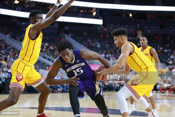 Noah Dickerson of the Washington Huskies loses control of the ball against Bennie Boatwright and Chimezie Metu of the USC Trojans during a firstround...