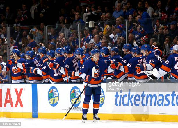 Noah Dobson of the New York Islanders is congratulated by his teammates after scoring his first career NHL goal against the Detroit Red Wings during...