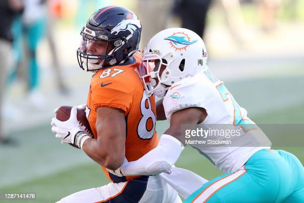 Noah Fant of the Denver Broncos carries the ball after making a catch against Eric Rowe of the Miami Dolphins during the second quarter at Empower...