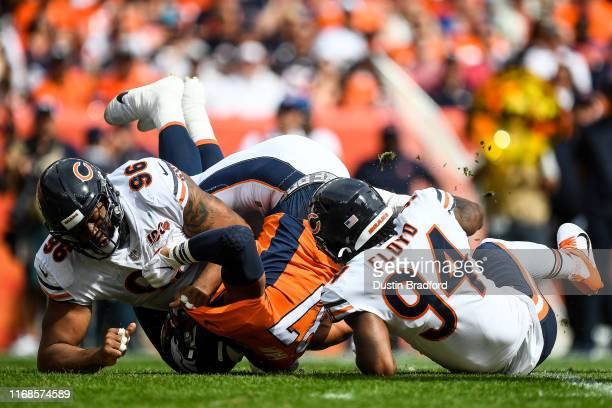 Noah Fant of the Denver Broncos is tackled by Leonard Floyd and Akiem Hicks of the Chicago Bears in the first quarter of a game at Empower Field at...