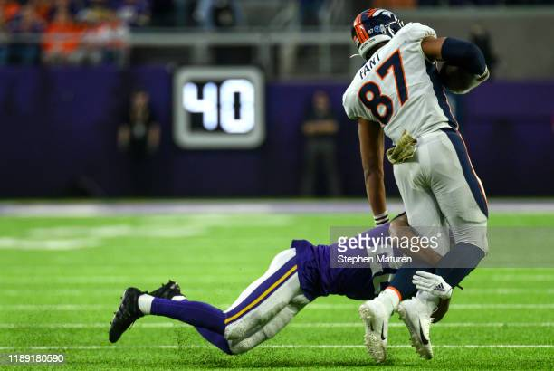 Noah Fant of the Denver Broncos is tackled with the ball by Trae Waynes of the Minnesota Vikings in the fourth quarter of the game at US Bank Stadium...