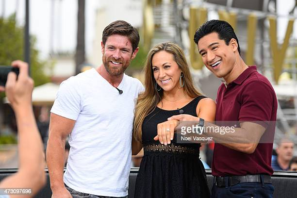 Noah Galloway Jamie Boyd and Mario Lopez display Jamie's engagement ring at Extra at Universal Studios Hollywood on May 12 2015 in Universal City...