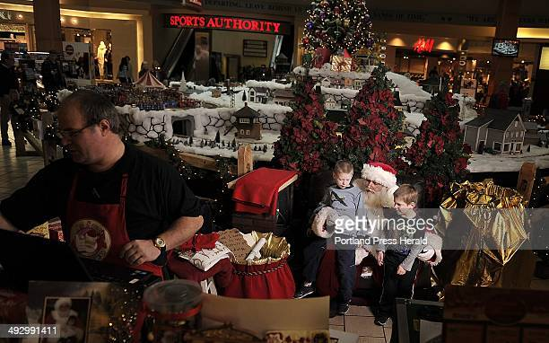 Noah Gardner gray shirt seven years old and Jayden Gardner black shirt five years old of Hartland get settled into Santa's lap at the Maine Mall in...