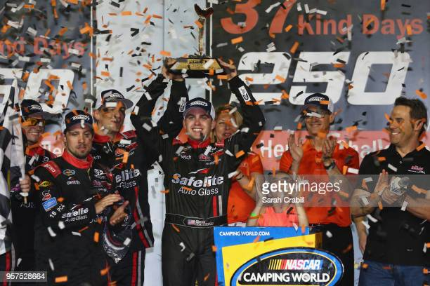 Noah Gragson driver of the Safelite Toyota poses with the trophy in victory lane after winning the NASCAR Camping World Truck Series 37 Kind Days 250...