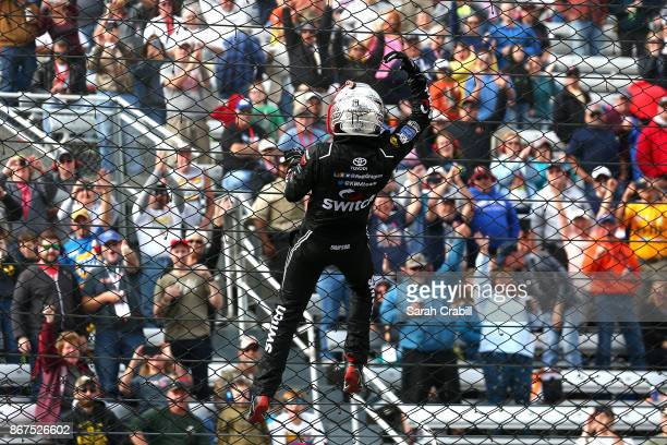 Noah Gragson driver of the Switch Toyota climbs the frontstretch fence after winning the NASCAR Camping World Truck Series Texas Roadhouse 200 at...
