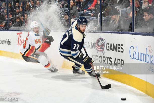 Noah Hanifin of the Calgary Flames and Josh Anderson of the Columbus Blue Jackets skate after a loose puck during the third period of a game on...