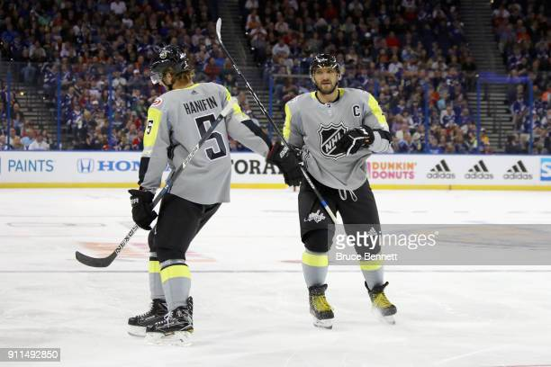 Noah Hanifin of the Carolina Hurricanes and Alexander Ovechkin of the Washington Capitals react after a goal in the first half during the 2018 Honda...