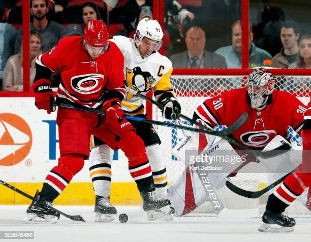 Noah Hanifin of the Carolina Hurricanes and Sidney Crosby of the Pittsburgh Penguins eye a rolling puck during an NHL game on February 23 2018 at PNC...