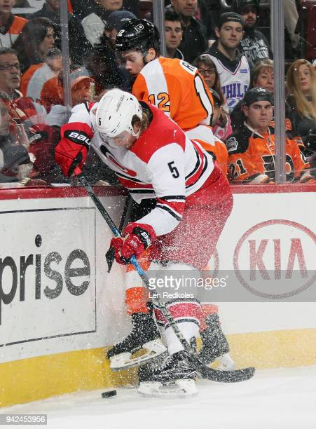 Noah Hanifin of the Carolina Hurricanes checks Michael Raffl of the Philadelphia Flyers into the boards as they pursue the loose puck on April 5 2018...