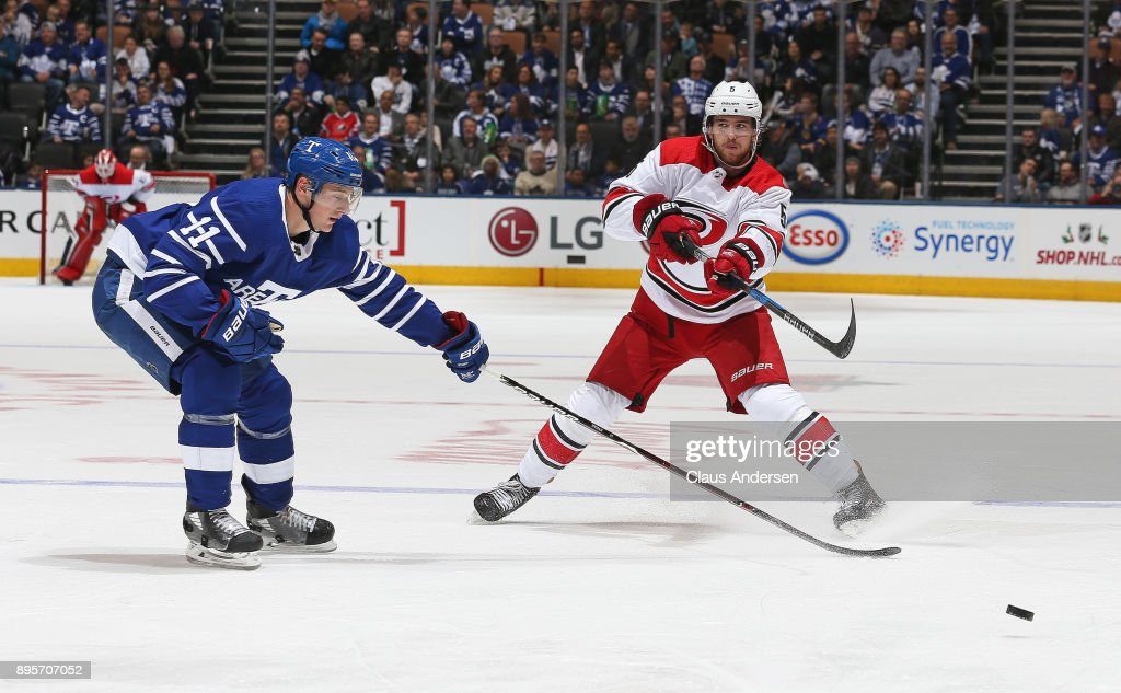 Noah Hanifin #5 of the Carolina Hurricanes fires a puck in past Zach Hyman #11 of the Toronto Maple Leafs during an NHL game at the Air Canada Centre on December 19, 2017 in Toronto, Ontario, Canada. The Maple Leafs defeated the Hurricanes 8-1.