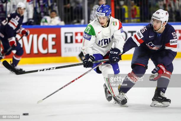 Noah Hanifin of USA and Simon Kostner of Italy fight for the puck during the 2017 IIHF Ice Hockey World Championship game between USA and Italy at...