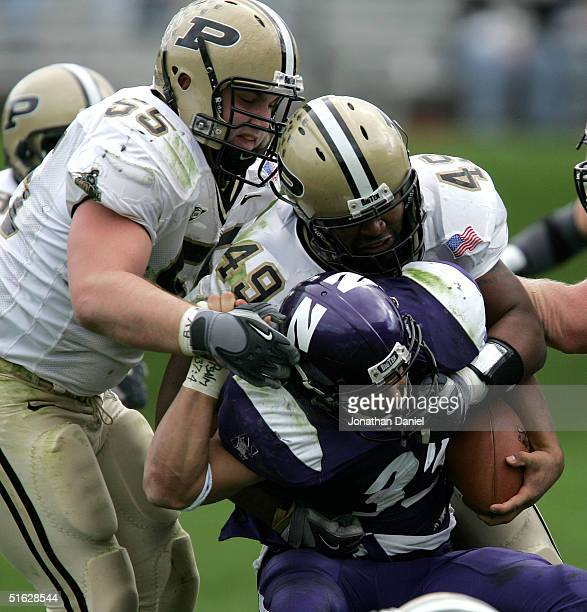 Noah Herron of Northwestern Wildcats is stopped by Brandon Villarreal and Anthony Spencer of Purdue Boilermakers on October 30 2004 at Ryan Field at...