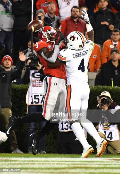 Noah Igbinoghene of the Auburn Tigers breaks up a pass against Jeremiah Holloman of the Georgia Bulldogs on November 10 2018 at Sanford Stadium in...