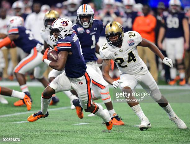 Noah Igbinoghene of the Auburn Tigers carries the ball against the Central Florida Knights during the ChickfilA Peach Bowl on January 1 2018 in...