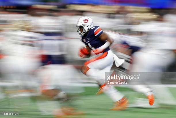 Noah Igbinoghene of the Auburn Tigers returns a kick in the first half against the UCF Knights during the ChickfilA Peach Bowl at MercedesBenz...