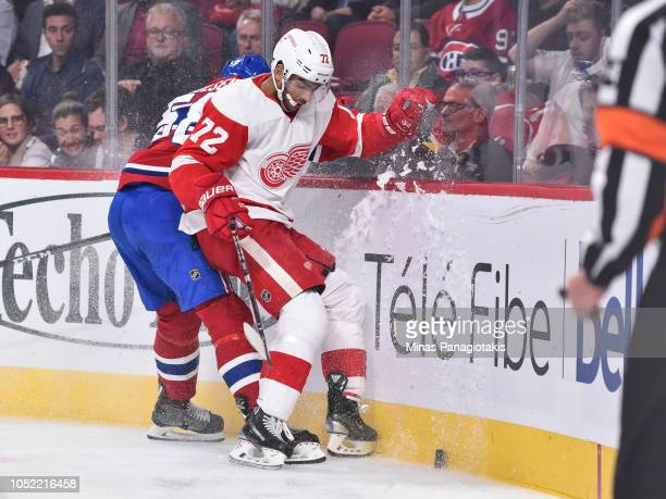 Noah Juulsen of the Montreal Canadiens and Andreas Athanasiou of the Detroit Red Wings chase the puck into the boards during the NHL game at the Bell...