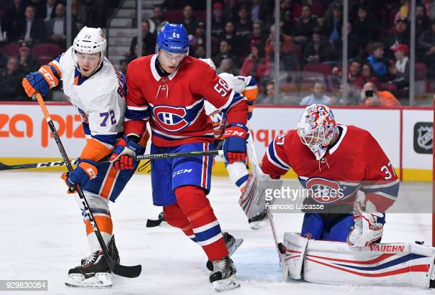 Noah Juulsen of the Montreal Canadiens defends against Anthony Beauvillier of the New York Islanders in the NHL game at the Bell Centre on February...