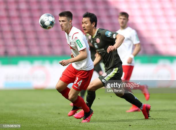 Noah Katterbach of 1. FC Koeln is challenged by Dong-won Ji of FSV Mainz 05 during the Bundesliga match between 1. FC Koeln and 1. FSV Mainz 05 at...