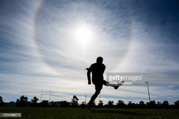 Noah Lolesio of the Brumbies practices kicking off a tee under an optical sun halo during a Brumbies Super Rugby training session at Brumbies HQ on...