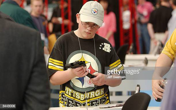 Noah Seiling 13 of Norwalk Ohio checks the cartridge on a semiautomatic pistol at the Taurus booth during the 133rd Annual National Rifle Association...