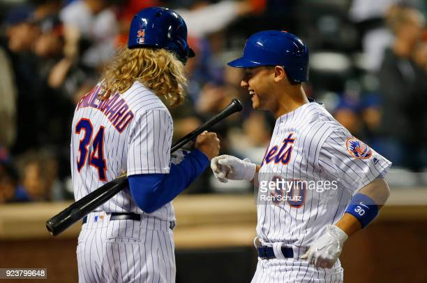 Noah Syndergaard congratulates teammate Michael Conforto of the New York Mets after hitting a homerun against the Miami Marlins during a game at Citi...