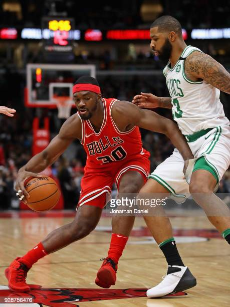 Noah Vonleh of the Chicago Bulls moves against Marcus Morris of the Boston Celtics at the United Center on March 5 2018 in Chicago Illinois The...