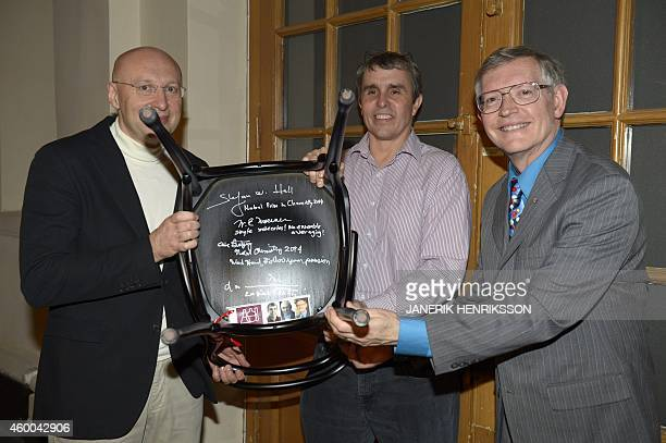 Nobel Chemistry laureates Stefan W Hell Eric Betzig and William E Moerner pose with their signed chair at the Swedish Academy in Stockholm Sweden on...