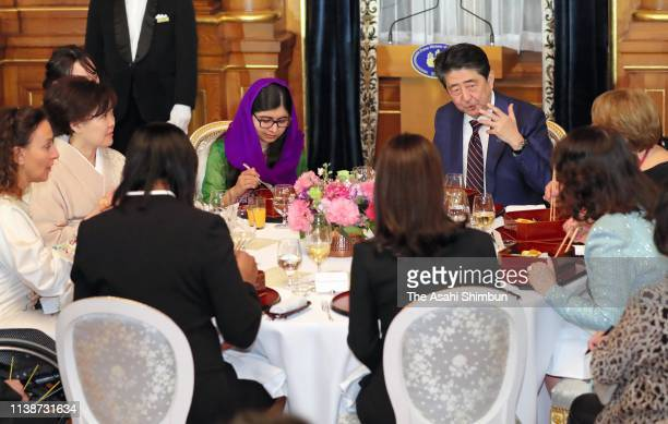 Nobel Peace Prize laureate Malala Yousafzai and Japanese Prime Minister Shinzo Abe talk during the dinner inviting attendees of the WAW! /W20 women's...