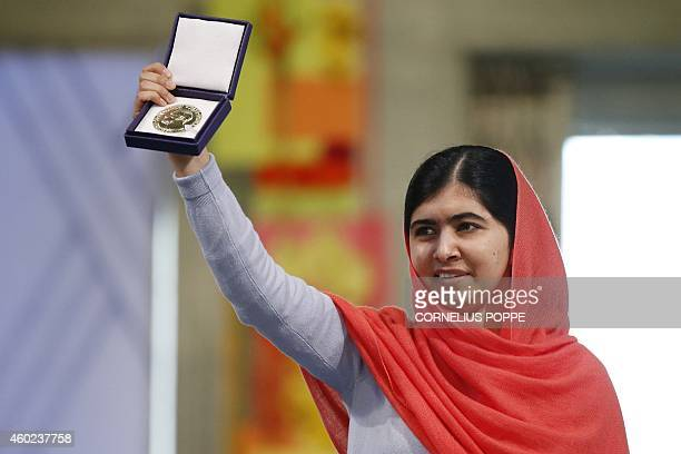 Nobel Peace Prize laureate Malala Yousafzai displays her medal during the Nobel Peace Prize awards ceremony at the City Hall in Oslo Norway on...