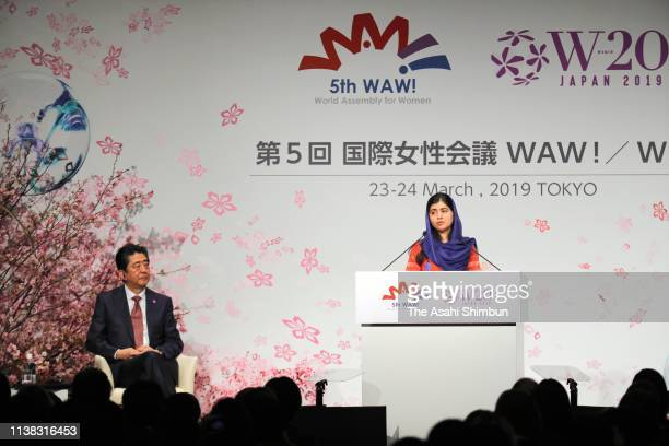 Nobel Peace Prize laureate Malala Yousafzai gives the keynote speech while Japanese Prime Minister Shinzo Abe listens during the World Assembly for...