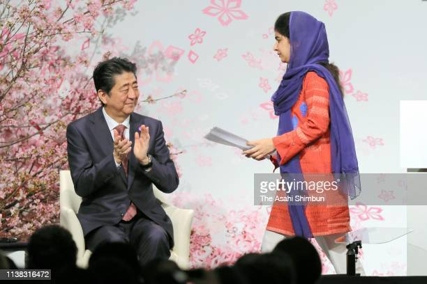 Nobel Peace Prize laureate Malala Yousafzai is applauded by Japanese Prime Minister Shinzo Abe after giving the keynote speech during the World...