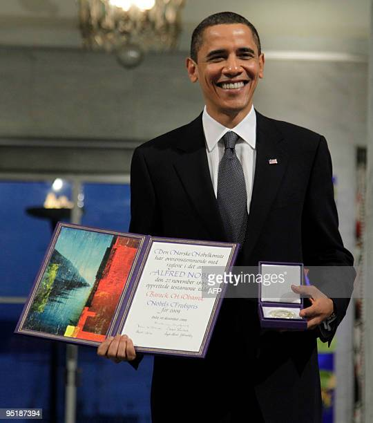 Nobel Peace Prize laureate US President Barack Obama poses with his diploma and medal during the Nobel Peace prize award ceremony at the City Hall in...