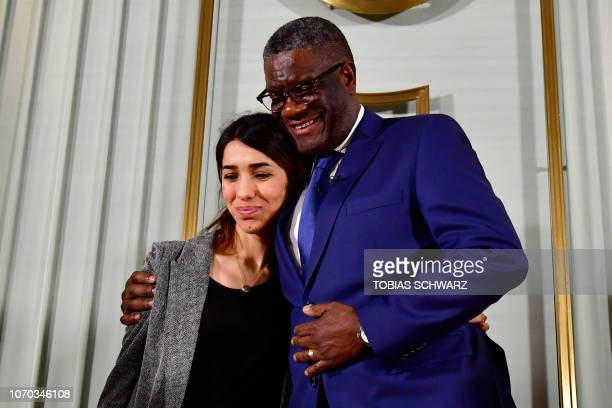 TOPSHOT Nobel Peace Prize laureates Congolese doctor Denis Mukwege and Yazidi activist Nadia Murad hug at the end of a press conference on December 9...
