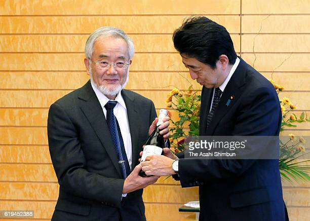 Nobel Prize in Medicine laureate and Tokyo Institute of Technology Honorary Professor Yoshinori Ohsumi presents a bottle of sake to Japanese Prime...