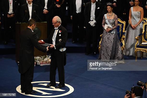 Nobel Prize in Medicine laureate Professor Shinya Yamanaka of Japan receives his Nobel Prize from King Carl XVI Gustaf of Sweden as Queen Silvia of...