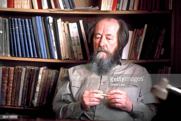 Nobel prizewinning author and critic of Soviet regimes Aleksandr Solzhenitsyn sitting nr bookshelf at his home