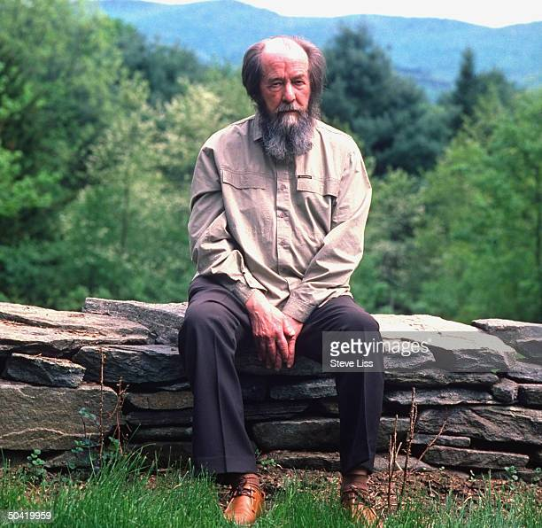 Nobel prizewinning author and critic of Soviet regimes Aleksandr Solzhenitsyn sitting on low stone wall outside his home