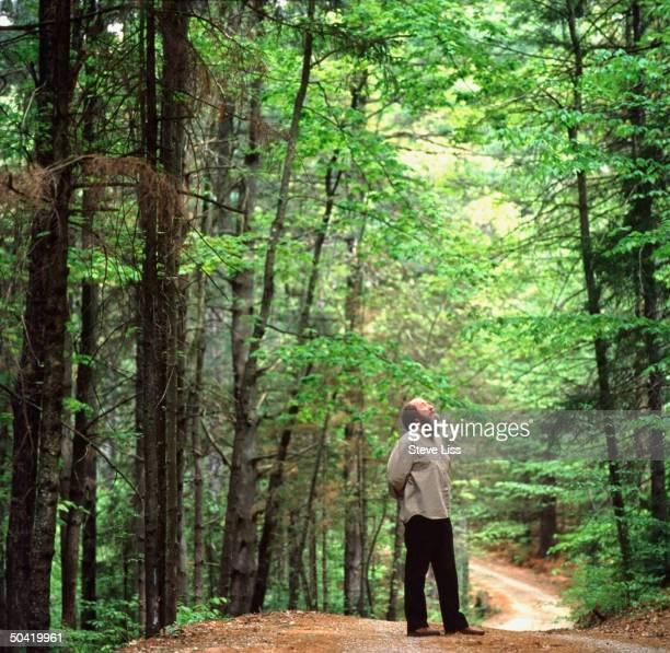 Nobel prizewinning author and critic of Soviet regimes Aleksandr Solzhenitsyn standing on path in woods nr his home looking up at trees