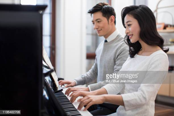 noble young couple playing the piano together - 一張羅 ストックフォトと画像