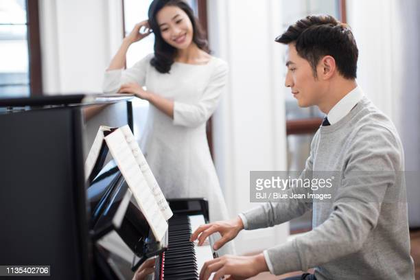noble young couple playing the piano together - ピアノ奏者 ストックフォトと画像