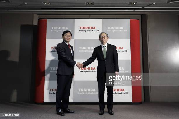 Nobuaki Kurumatani incoming chief executive officer and chairman of Toshiba Corp left shakes hands with Satoshi Tsunakawa outgoing chief executive...