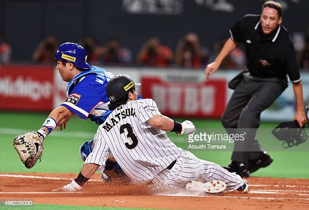 Nobuhiro Matsuda of Japan slides safely into the home to score by a sacrifice fly of Hayato Sakamoto while catcher Kang Minho of South Korea tries to...