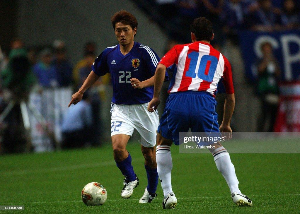 Nobuhisa Yamada of Japan and Carlos Bonet of Praguay compete for the ball during the international friendly match between Japan and Paraguay at Saitama Stadium on June 11, 2003 in Saitama, Japan.