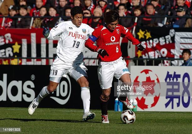 Nobuhisa Yamada of Urawa Red Diamonds and Hulk whose real name is Givanildo Vieira de Souza of Kawasaki Frontale compete for the ball during the 85th...