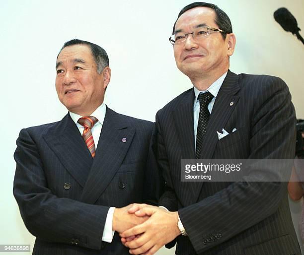 Nobukazu Muto, president of Isetan Co., left, and Kunio Ishizuka, president of Mitsukoshi Ltd., shake hands following a joint news conference in...