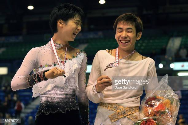 Nobunari Oda of Japan celebrates his bronze medal win with Yuzuru Hanyu of Japan who took the silver in the men's free program on day two at the ISU...