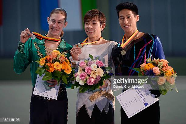 Nobunari Oda of Japan, Jason Brown of the United States and Jeremy Ten of Canada pose at the victory ceremony of the Men's competition during day...