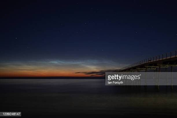 Noctilucent clouds can be seen above the horizon beyond Saltburn pier on June 01 2020 in Saltburn By The Sea United Kingdom Noctilucent clouds or...