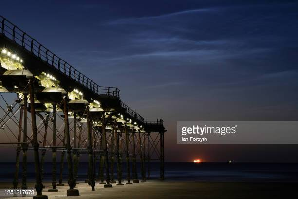 Noctilucent clouds can be seen above the horizon beyond Saltburn pier on June 22 2020 in Saltburn By The Sea United Kingdom Noctilucent clouds or...