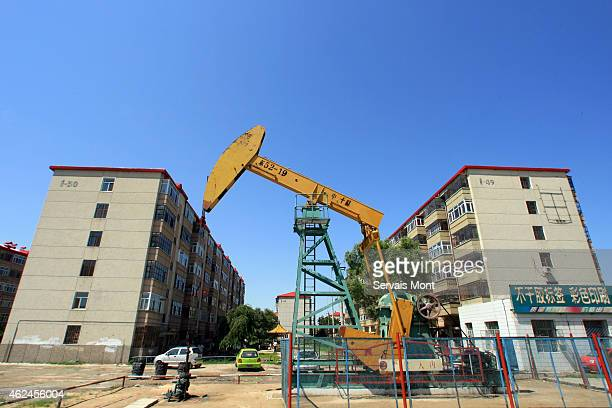 A CNPC nodding donkey oil pump pumps oil in the middle of a residential complex on July 14 2006 in Daqing Heilongjiang province China China National...